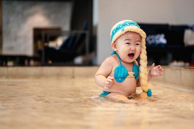 A menina está usando maiô e usa uma linda peruca dourada se divertindo na piscina