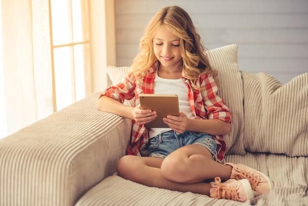 A menina está usando uma tabuleta digital e ao sentar-se no sofá.