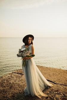 A menina está vestida com um vestido de noiva longo azul e um chapéu preto.