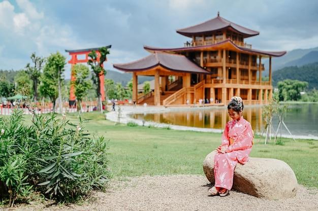 A menina está vestindo um quimono feliz sentado em uma pedra