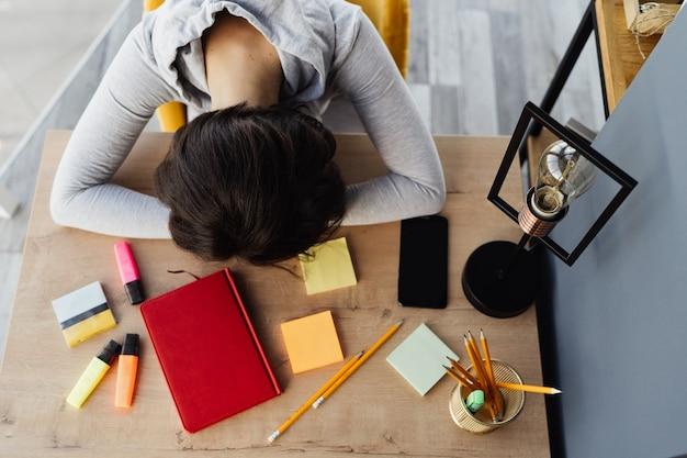 A menina estava cansada de trabalhar e adormeceu no local de trabalho