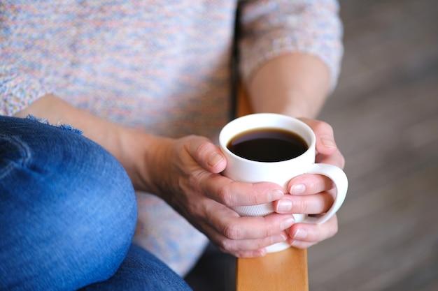 A menina estava sentada confortavelmente em uma cadeira segurando uma xícara de café