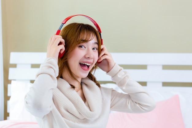 A menina estava usando fones de ouvido e curtindo música na cama