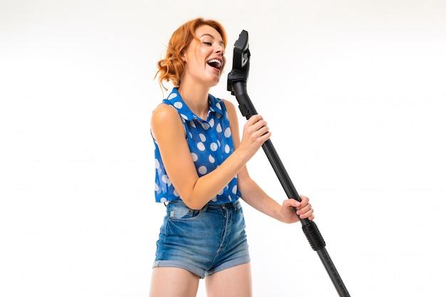 A menina europeia da dona de casa com um aspirador de pó na mão canta em um fundo branco