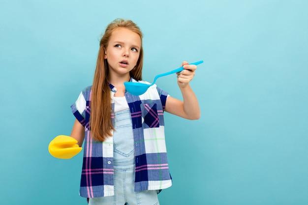 A menina européia de sorriso prova com uma colher em suas mãos na parede azul clara