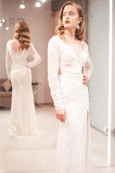 A menina experimenta um elegante vestido de noiva
