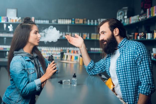A menina fala com o homem alto do vendedor com cabelo longo e uma barba.
