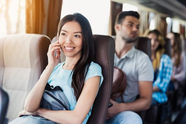 A menina fala no curso dos passageiros do telefone pelo ônibus de excursão.