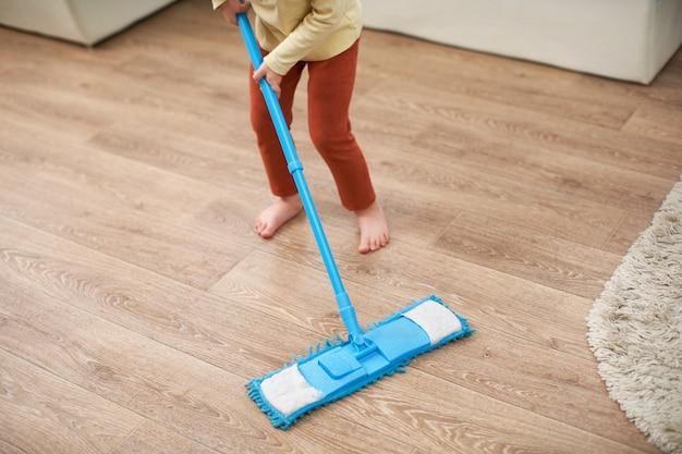 A menina faz a limpeza do quarto
