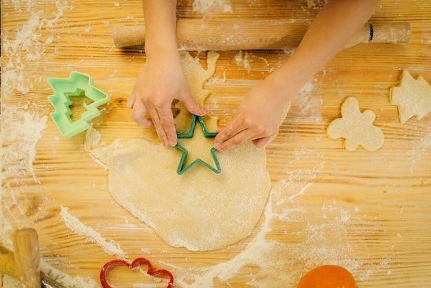 A menina faz biscoitos em forma de coração
