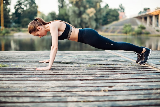 A menina faz flexões na plataforma de madeira na margem do rio
