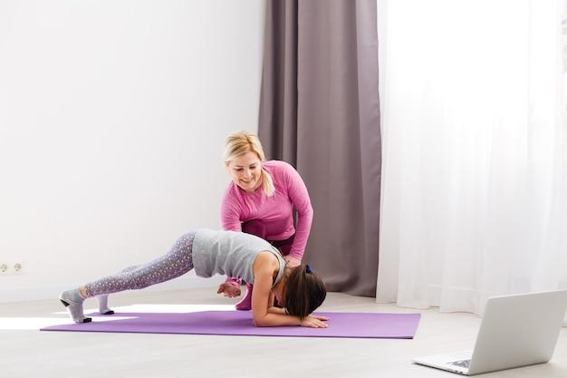 A menina faz ginástica em casa. vídeo tutorial de ginástica. exercícios de ginástica. a ideia de uma atividade infantil em quarentena