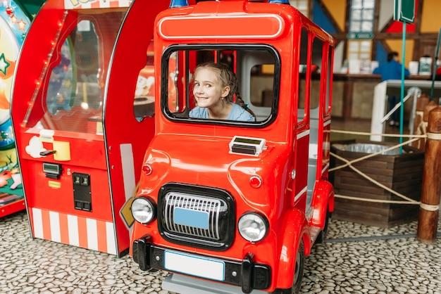 A menina faz o papel de motorista de ônibus, máquina de jogo