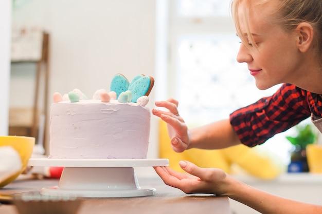A menina faz um bolo de páscoa na cozinha.