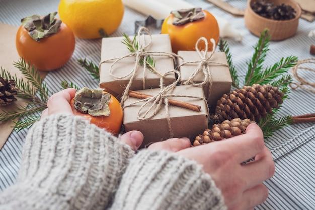 A menina faz uma composição de presentes de ano novo embalado com as próprias mãos em papel kraft, vista de cima, close-up. fundo de natal feliz. preparando-se para o feriado. conceito de natal.