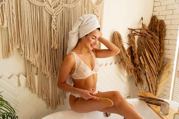 A menina faz uma massagem para si mesma com uma escova na banheira. ela tem lindas pernas bronzeadas. ela faz massagem anti-celulite linfática