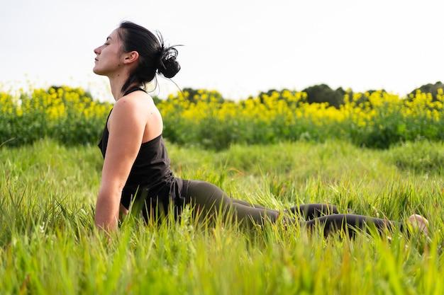 A menina faz uma postura de ioga na natureza