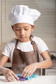 A menina fazendo biscoitos na cozinha.