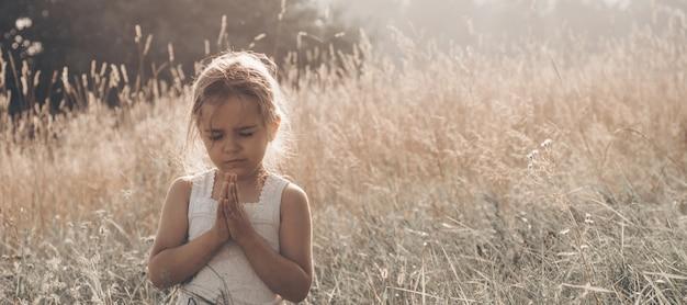 A menina fechou os olhos, orando ao ar livre, mãos postas em conceito de oração pela fé, espiritualidade e religião. paz, esperança, conceito de sonhos.