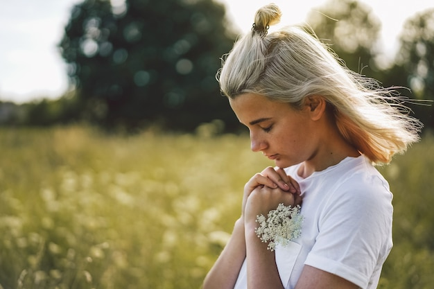 A menina fechou os olhos, orando em um campo. mãos postas em conceito de oração pela fé