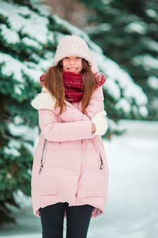 A menina feliz aprecia o inverno e o tempo da neve ao ar livre no dia de inverno bonito
