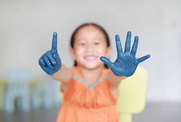 A menina feliz com suas mãos azuis pintou mostrar um e cinco dedos na sala das crianças.