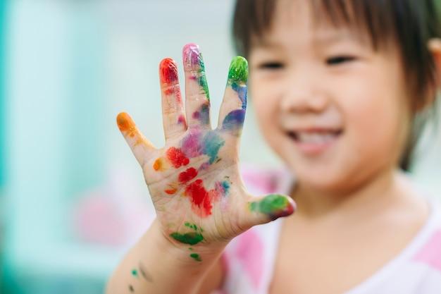 A menina feliz e bonito usa as mãos e os dedos para o trabalho de arte da pintura do dedo.