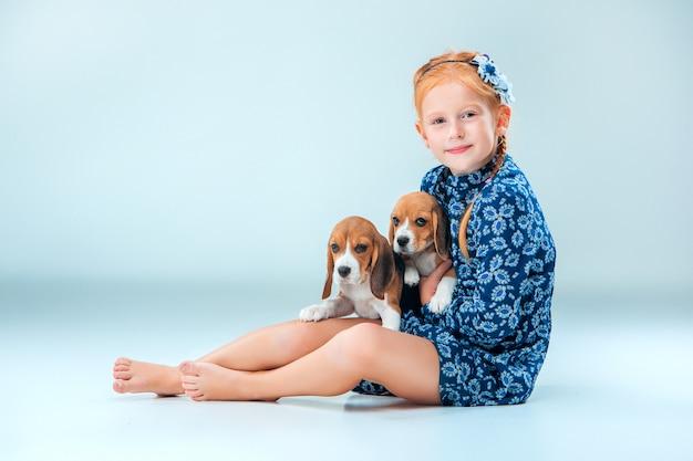 A menina feliz e dois filhotes de cachorro beagle
