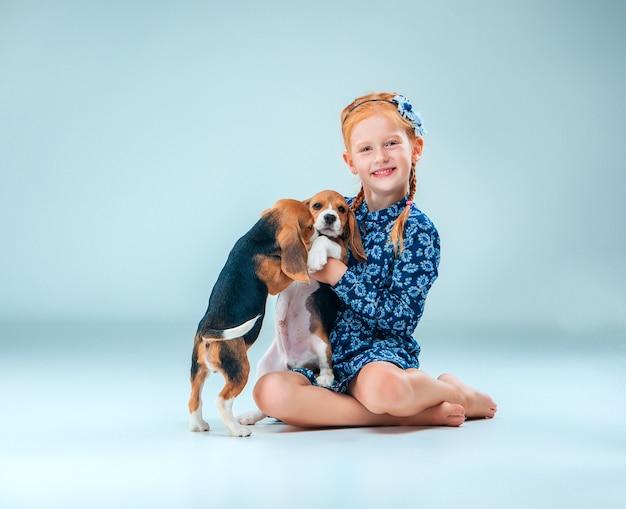 A menina feliz e filhote de cachorro beagle dois em fundo cinza