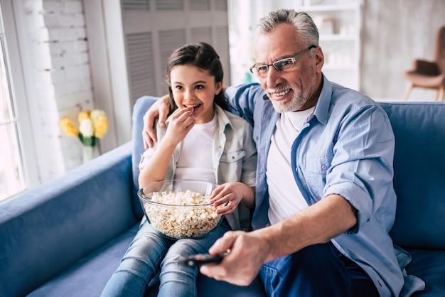 A menina feliz e um avô assistindo televisão com uma pipoca
