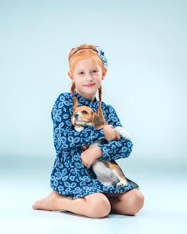 A menina feliz e um filhote de cachorro beagle em fundo cinza