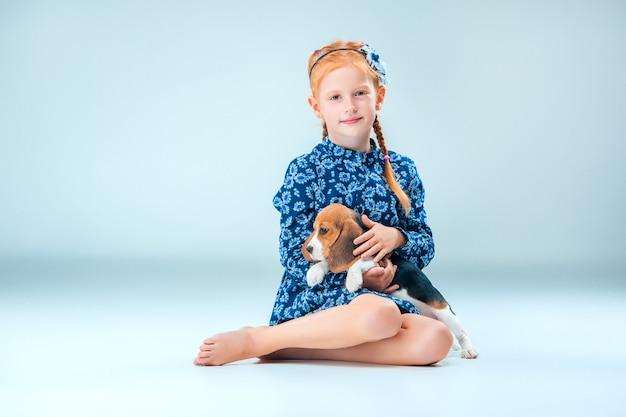 A menina feliz e um filhote de cachorro beagle na parede cinza