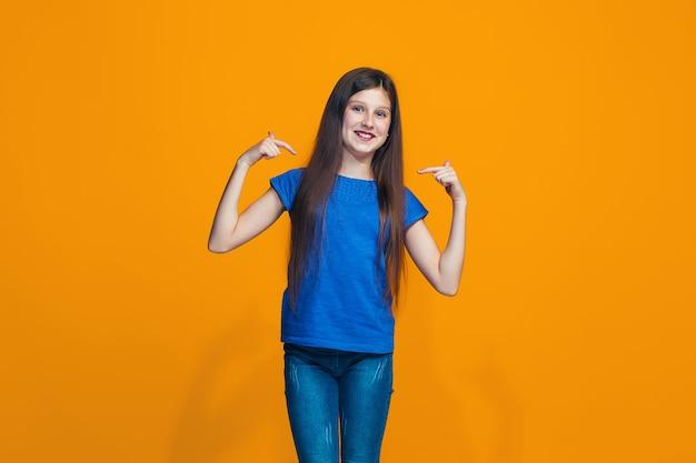 A menina feliz em pé e sorrindo contra a parede laranja