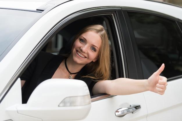 A menina feliz espreita para fora a janela de carro.