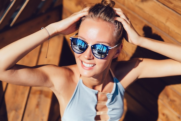 A menina feliz no roupa de banho e nos óculos de sol, toma um sunbathe, apreciando o verão.