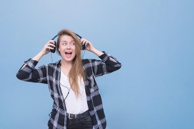 A menina feliz nos fones de ouvido em um fundo azul olha de lado o lugar para o texto.