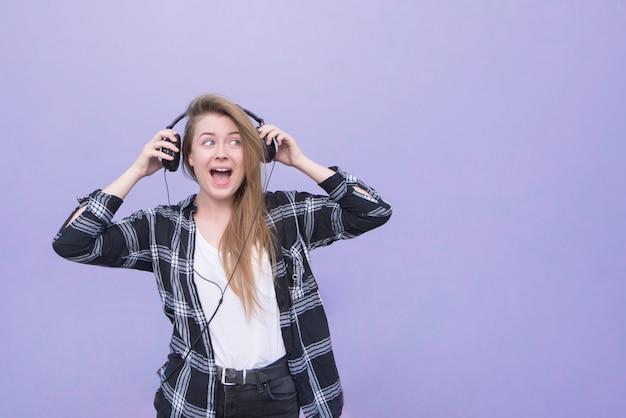A menina feliz nos fones de ouvido em um fundo roxo olha de lado o lugar para o texto. retrato de uma menina sorridente, ouvindo música e isolado em um fundo roxo. copyspace