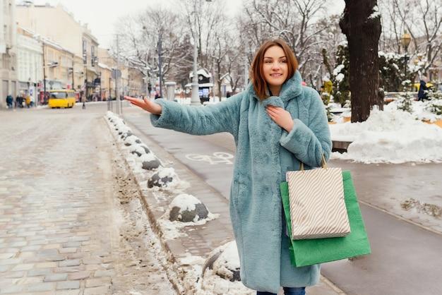 A menina feliz nova com sacos de compras trava um táxi.