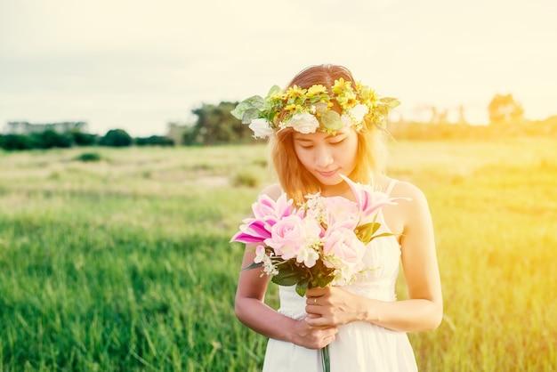 A menina feliz olhando para ela bouquet ao pôr do sol