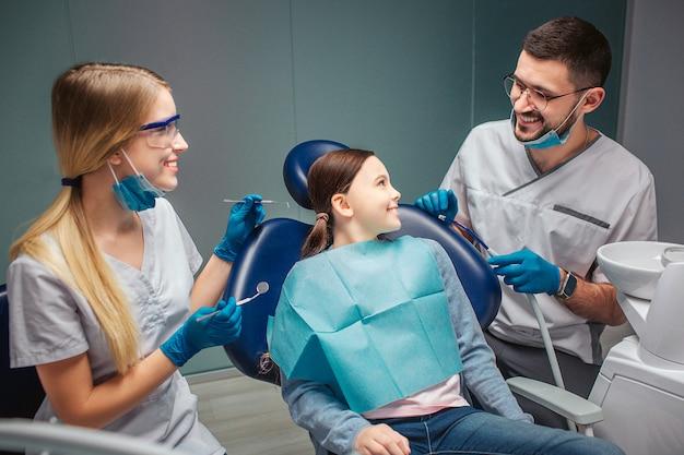 A menina feliz positiva senta-se na cadeira dental e olha-se e dentista masculino