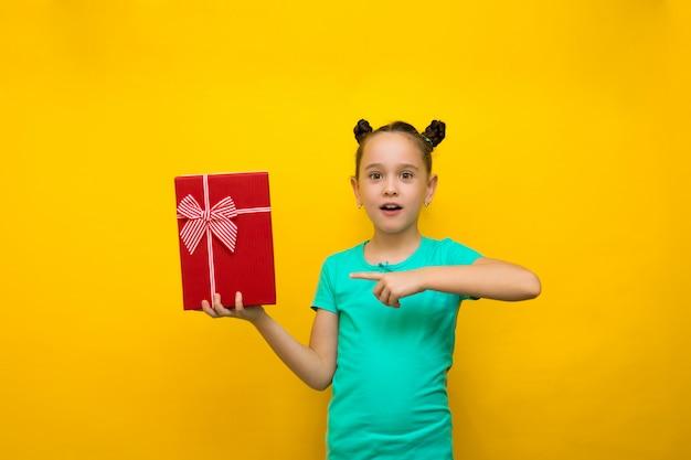 A menina feliz que está isolada sobre o fundo amarelo aponta na caixa de presente vermelha na surpresa.