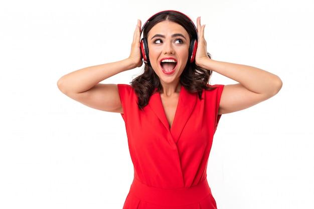 A menina feliz sorri amplamente em uma senhora branca e elegante em um vestido vermelho ouve música com fones de ouvido