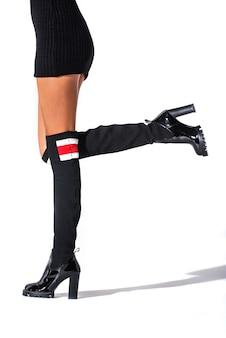 A menina fica em botas de hessian preto nos pés de um modelo em um fundo branco