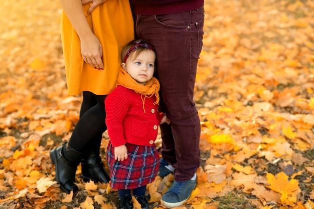 A menina fica pensativa e sozinha ao lado dos pais, segurando-os pelas pernas