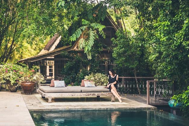 A menina fica perto de uma piscina privada e de uma bela e antiga vila em bali.