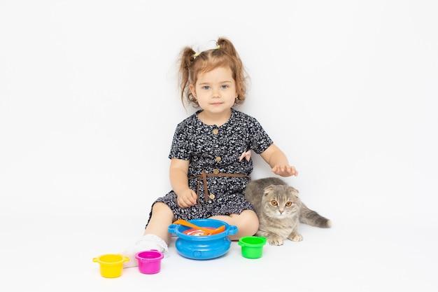 A menina finge brincar de preparar comida no fundo branco