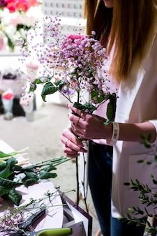 A menina florista cria um buquê suave de gypsophila e rosas atrás do balcão no mercado de flores