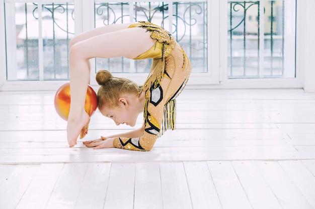 A menina fofa faz ginástica com uma bola