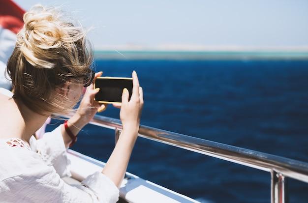 A menina fotografa a paisagem marinha
