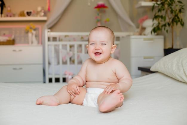 A menina gorda bonito da criança sorri nas fraldas que sentam-se na cama em casa